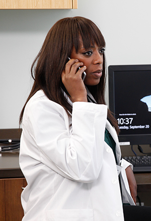 Healthcare provider talking on the phone in an exam room