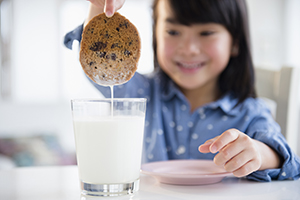 Young girl dunking a cookie in a glass of milk